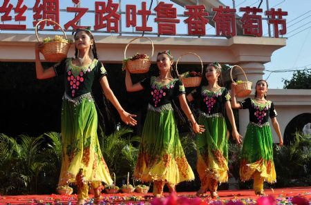 Girls perform during the opening ceremony of the 18th Grape Festival of Turpan on China's Silk Road, in Turpan, northwest China's Xinjiang Uygur Autonomous Region, Aug. 26, 2009. The festival since 1990 includes singing and dancing galas, symposiums on Silk Road tourism and on China's grape cultivation, cuisine contests for local snacks, and trade fairs as well.(Xinhua/Zhao Ge)