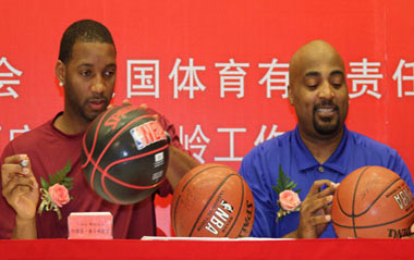 NBA player Tracy McGrady (L) of Houston Rockets signs on a basketball which is going to be auctioned during an opening ceremony and a press conference of Warming China Charity Tour sponsored by the China Red Cross Foundation in Beijing, capital of China, Aug. 31, 2009.