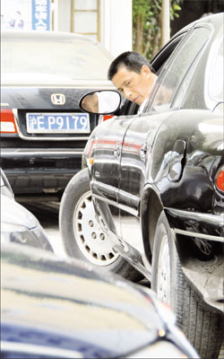 Guard Gao Henglun reverses a car carefully at Huajiao Apartments. [Shanghai Daily]