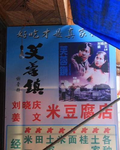 Local businessmen sell posters of the movie 'Hibiscus Town' to tourists. [Photo:CRIENGLISH.com/Duan Xuelian]