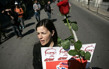 A woman carries a flower and a poster with the image of former Chilean President Salvador Allende, during a rally marking the 36th anniversary of the coup that ousted president Salvador Allende and brought General Augusto Pinochet to power, in Santiago, capital of Chile, Sept. 11, 2009.