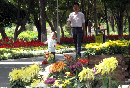 A man with his son enjoys the flowers at an arboretum in Urumqi, northwest China's Xinjiang Uygur Autonomous Region, on Saturday, Sept. 12, 2009. (Xinhua/Shen Qiao)