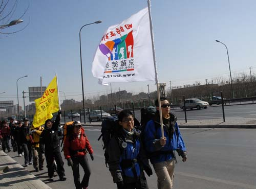 The group marching along the road in a single-file line. The white banner was the logo for the march. As the group met people along the way, they invited them to sign the yellow banner. 队伍排成一列纵队向前走。白色旗帜是一路上行进的标志。他们邀请遇到的人在黄色旗帜上签名。