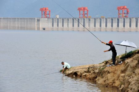 Two locals go fishing near the Three Gorges reservoir in Yichang, a city of central China's Hubei Province, Sept. 15, 2009. The operation to raise the water level of the Three Gorges reservoir to 175 meters began early Tuesday.