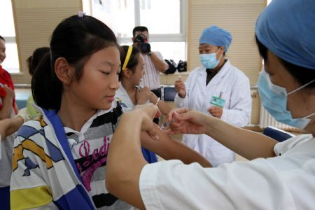 Pupils get flu vaccination shots at Hepingli No.9 Primary School in Dongcheng District of Beijing, capital of China, Sept. 16, 2009. Free vaccinations will be provided to 1.8 million residents in Beijing including senior people aged 60 or older as well as all primary and middle school students from Sept. 10 to Oct. 31 this year. (Xinhua/Zhou Liang)
