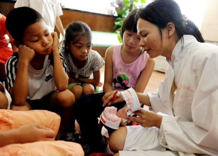 A doctor teaches children oral health knowledge in Nanning, southwest China's Guangxi Zhuang Autonomous Region, on Sept. 20, 2009.(Xinhua/Zhang Ailin)