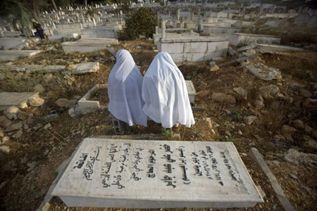 Palestinian women pray next to a grave in a cemetery on the first day of the Muslim holiday of Eid al-Fitr in the West Bank city of Ramallah September 20, 2009.
