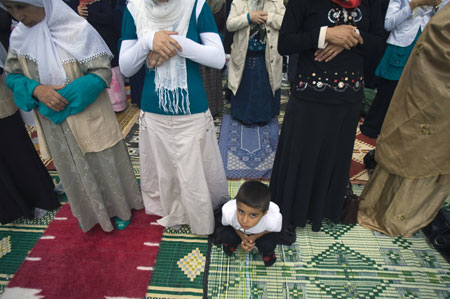 A boy sits as women pray at the Eyup Sultan mosque during Eid al-Fitr prayers in Istanbul September 20, 2009.