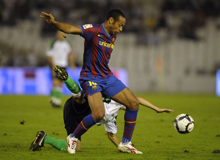 Barcelona's Thierry Henry (top) battles for the ball with Racing Santander's Manuel Arana during their Spanish First Division soccer match at Santander's El Sardinero stadium September 22, 2009.