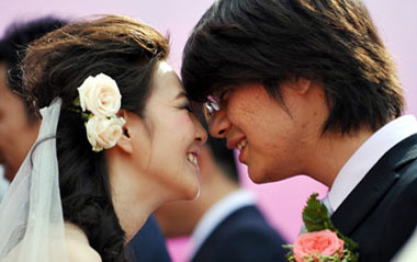 A groom prepares to kiss his bride during a mass wedding in Qingdao, east China's Shandong Province, Sept. 27, 2009. The mass wedding, under the theme of 'blessing the homeland', was attended by 60 couples. The 60th anniversary of the founding of the People's Republic of China will be celebrated on Oct. 1.