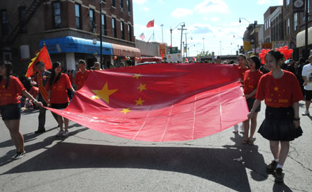 Girls hold the national flag of the People's Republic of China during a parade in Chinatown of Chicago, the United States, on Sept. 27, 2009. The parade was held here on Sunday to celebrate the upcoming 60th anniversary of the founding of the People's Republic of China. (Xinhua/Hu Guangyao)