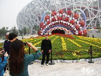 Tourists pose for photos beside a huge parterre in front of the National Stadium or 'Bird's Nest' in Beijing, capital of China. The Olympic Park in which the Bird's Nest is located has been decorated to celebrate the 60th anniversary of the founding of the People's Republic of China which falls on Oct. 1. [Photo by Hu Junfeng]