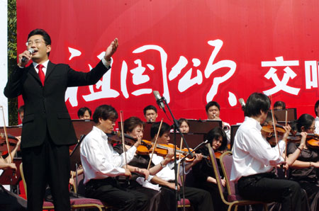 A performer elocntes emotionally during a symphonic poem recitation show of Ode to Homeland, an outdoor public performance at the side of the West Lake with the musical obbligato by a symphony orchestra, in close range with the audience, in Hangzhou, capital of east China's Zhejiang Province, Oct. 2, 2009. (Xinhua/Shi Jianxue)