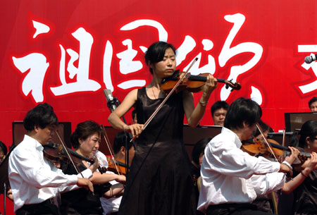 A violinist leads playing of the accompanying tune during a symphonic poem recitation show of Ode to Homeland, an outdoor public performance at the side of the West Lake with the musical obbligato by a symphony orchestra, in close range with the audience, in Hangzhou, capital of east China's Zhejiang Province, Oct. 2, 2009. (Xinhua/Shi Jianxue)