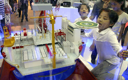 Kids view the model of deep sea oil drilling and storage platform at the Progressive Jiangsu -- Grand Exposition of Achievements in Celebration of the 60th Anniversary of the Founding of the People's Republic of China, at the Nanjing International Expo Center, in Nanjing City, capital of east China's Jiangsu Province, Oct. 2, 2009. (Xinhua/Dong Jinlin)