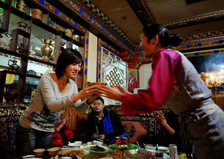 Picture shows a tourist from Beijing accepting blessing from her Tibetan friend in Nyingchi Prefecture, southeastern Tibet, Oct. 9, 2009. (Xinhua Photo)