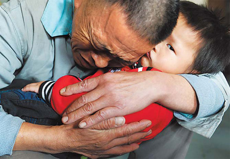 Wang Bangyin, a farmer from Zunyi, Guizhou province, breaks down as he holds his rescued son at Guiyang Welfare Center for Children yesterday after the pair were reunited. Wang's son was among 60 children seeking parents after police freed them from human traffickers. The Ministry of Public Security released photos of the children on Tuesday. Wang and his son were the first from the list to be reunited.