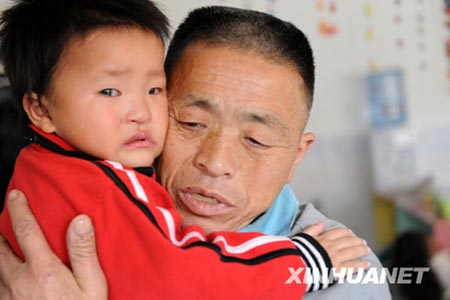 Wang Bangyin, a farmer from Zunyi, Guizhou Province, holds his rescued son at Guiyang Welfare Center for Children yesterday after the pair were reunited. Wang's son was among 60 children seeking parents after police freed them from human traffickers. The Ministry of Public Security released photos of the children on Tuesday. Wang and his son were the first from the list to be reunited. [China Daily]