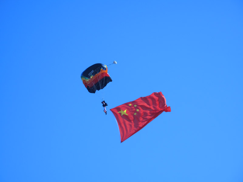 Photo taken on November 15 shows a flag of the PLA flows during a bailout performance of an air force show in Beijing Shahe airport. [Jiang Yiping/China.org.cn]