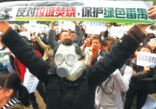 """A masked protester makes a point as more than 1,000 residents demonstrate outside the Guangzhou government building yesterday. The sign reads: """"Oppose garbage burning, protect green Panyu."""" [China Daily]"""