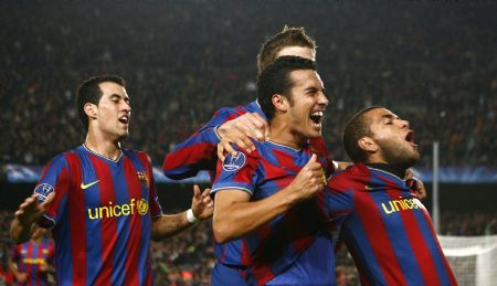 Barcelona's Pedro Rodriguez (C) celebrates with teammates Dani Alves (R) and Sergio Busquets after scoring against Inter Milan during their Champions League soccer match at Nou Camp stadium in Barcelona November 24, 2009.
