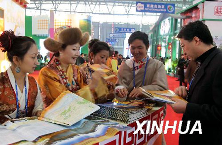 A businessman consults staff at the Tibetan booth at the China International Tourism Trade Fair held in Kunming, capital of southwest China's Tibet Autonomous Region, on Nov. 19, 2009. (Xinhua Photo)