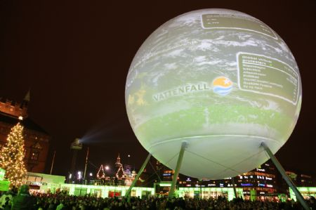 A giant model of the earth is illuminated by electricity generated by people's riding bicycles in front of the city hall of Copenhagen, Denmark, Dec. 7, 2009, on the occasion of the United Nations Climate Change Conference (COP15). [Lin Miao/Xinhua]