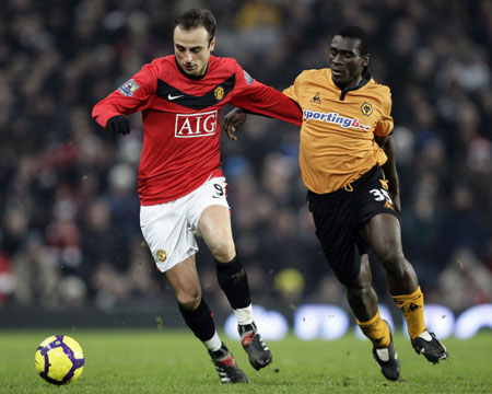 Manchester United's Dimitar Berbatov (L) holds off Wolverhampton Wanderers' Segundo Castillo during their English Premier League soccer match at Old Trafford in Manchester, northern England, December 15, 2009. [Xinhua/Reuters]