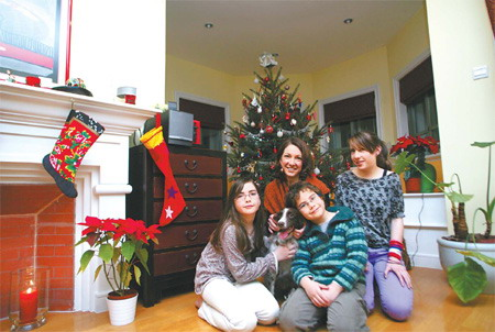 Marie Finn (second from left) and her children in their home. [Guan Xin/China Daily]