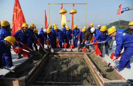 Construction workers pour concrete to a building of the new Beichuan Middle School, in Beichuan county, southwest China's Sichuan Province, Dec. 28, 2009. [Jiang Hongjing/Xinhua]