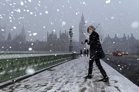 A girl walks across Westminster Bridge during snowfall in London January 6, 2010. Blizzards swept across central and southern England on Wednesday, bringing more road and rail chaos, forcing airlines to suspend flights and hundreds of schools to close. [Chinadaily.com.cn via agencies]