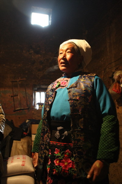 A Qiang woman shows the rice she received from the government in Buwa village, Sichuan Province. [China.org.cn/ Zhao Xi]