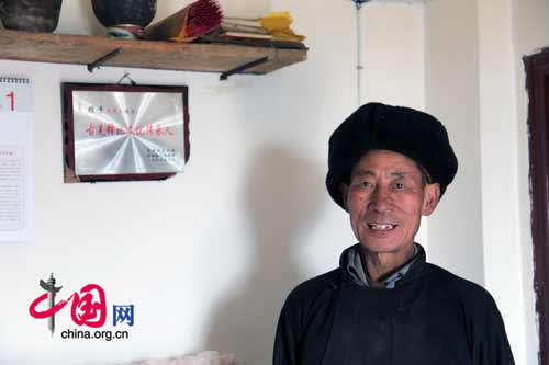 The only surviving Shibi in Luobo Village, Wang Mingjie stands in his new home. The plaque says 'The Inheritor of Qiang Shibi Culture.'