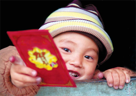 A boy in Hunan province grabs a red envelope he got during the Spring Festival. [China Daily]
