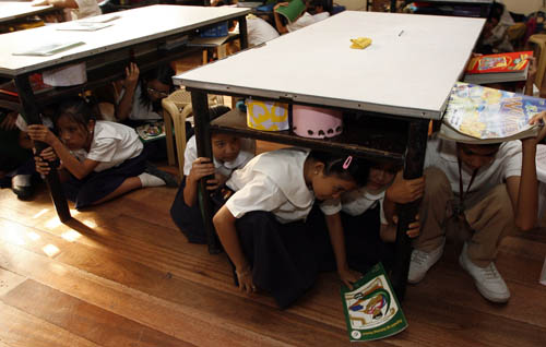 students take cover under tables during an earthquake drill at san juan elementary school in san