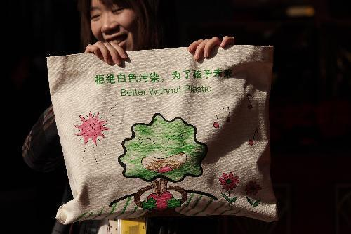 A staff member displays a reusable bag which is handed out to members of the 11th National Committee of the Chinese People's Political Consultative Conference (CPPCC) for carrying meeting materials during the CPPCC session in Beijing, China, March 2, 2010. The Third Session of the 11th CPPCC National Committee is scheduled to open on March 3. [Xing Guangli/Xinhua]