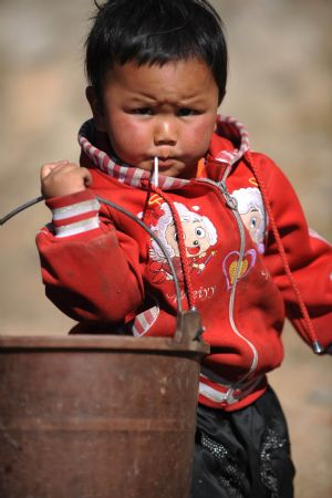 A child queues for water at Dongshan Town of Xuanwei City, southwest China's Yunnan Province, on March 5, 2010. Drought had affected 61.31 million Mu (4.09 million hectares) of farmland in southwestern China as of March 5, according to the latest figure from the Ministry of Agriculture (MOA). [Xinhua]