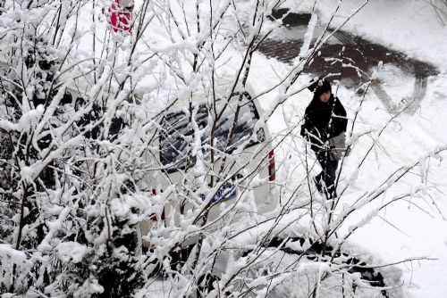 Residents walk in snow in Shenyang, capital of northeast China's Liaoning Province, on March 15, 2010. A heavy snow hit Shenyang Sunday night, bringing fresh air to the city but causing troubles on the road as well.[Xinhua]