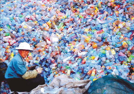 A man sorts empty plastics bottles into different categories at a garbage recycling plant in the suburbs of Huaibei, a city in Anhui province. China consumes 52 million tons of plastics a year. [China Daily]