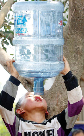 A boy squeezes the last drop from a mineral water bottle in Wulong county, Chongqing, on Saturday. The area is suffering from one of the severest droughts in history. [Xinhua]