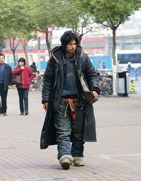 An undated photograph of a homeless man, nicknamed Brother Sharp for his good looks and sharp dress sense, wandering the streets of Ningbo, Zhejiang province, was rose to internet fame.[www.tianya.cn]