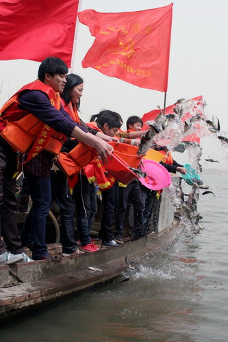 Volunteers free various kinds of fish into Xiazhu lake, a state-level wet-land park in Deqing county, Zhejiang province on March 21, 2010, to mark the 18th World Water Day which falls on March 22. People in different regions of the nation have organized a series of activities to promote water quality.[Xinhua]