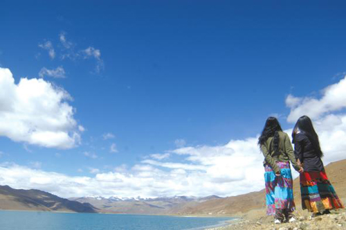 An undated photo shows two visitors doing             sightseeing by the Yamdrok Yumtso Lake in Shannan Prefecture,             southeastern Tibet.[Photo: Lhasa Evening News]