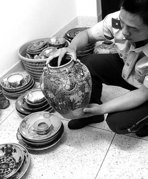 A police officer displays the pottery and porcelain artifacts salvaged from the sunken ancient merchant ship Nan'ao No 1 on June 8, 2007. [Xinhua]