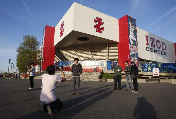 Fans take pictures in front of the Izod Center before the start of an NBA basketball game between the New Jersey Nets and Charlotte Bobcats in East Rutherford, New Jersey April 12, 2010.(Xinhua/Reuters Photo)