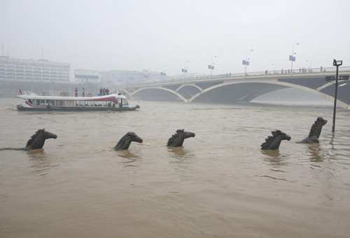 Water rises to its highest level this year in the Guilin section of Lijiang River in the Guangxi Zhuang autonomous region on Monday, submerging statues on a pedestrian pathway along the river as a result of continuous rainfall. Rainfall in the past days in Guangxi, Yunnan and Guizhou has eased the prolonged drought in Southwest China. [Xinhua]