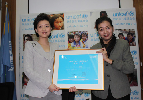 Dr. Yin Yin Nwe, UNICEF China Representative, presents a certificate to Yang Lan.