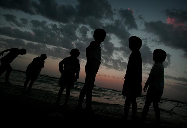 Palestinian boys enjoy the sunset on a beach in Gaza Strip, April 27, 2010. (Xinhua/Yasser Qudih)