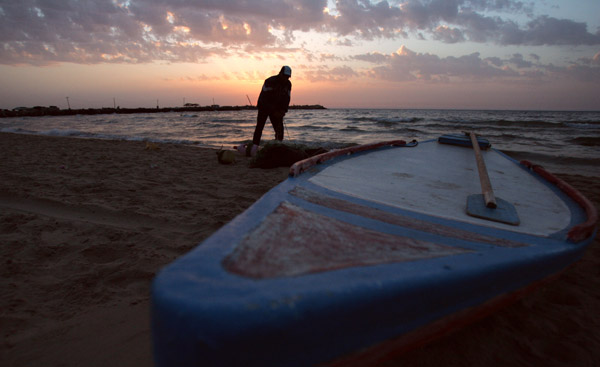 A Palestinian fisherman prepares his net at the sunset in Gaza Strip, April 27, 2010. [Xinhua/Yasser Qudih]