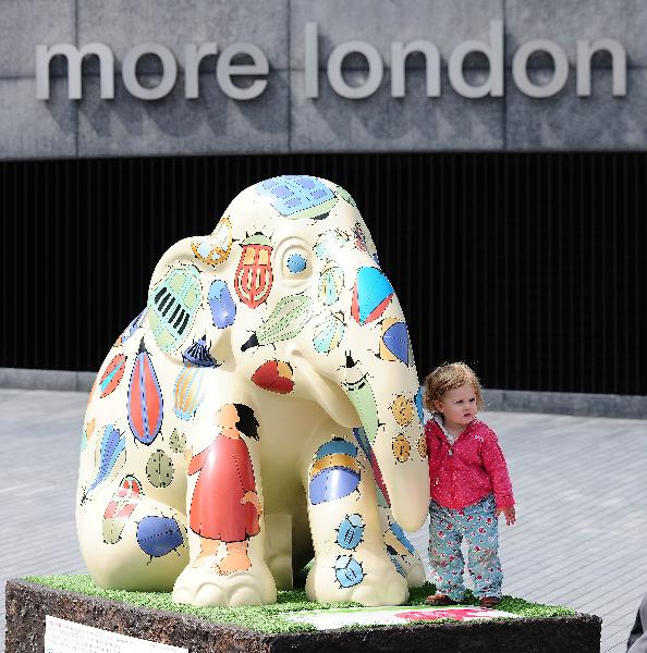 A little boy stands besides a painted elephant sculpture near Tower Bridge in London, capital of Britain, May 5, 2010. Over 250 brightly painted life-size elephant sculptures have been located over central London recently. This is a conservation campaign that shines a multi-coloured spotlight on the urgent crisis faced by the endangered Asian elephant. The art works will be put into auction aiming to raise fund for the Asian elephants. (Xinhua/Zeng Yi)
